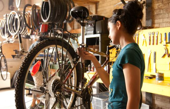 A young woman working on a bike.