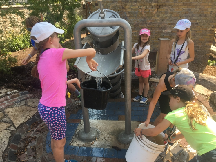 Campers playing with new water elements in the Children's Garden
