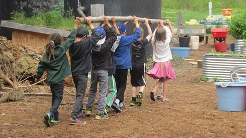 Children holding log above their heads.