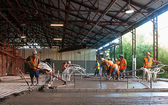 Construction workers smoothing concrete in the historic kiln building during construction, summer 2017.