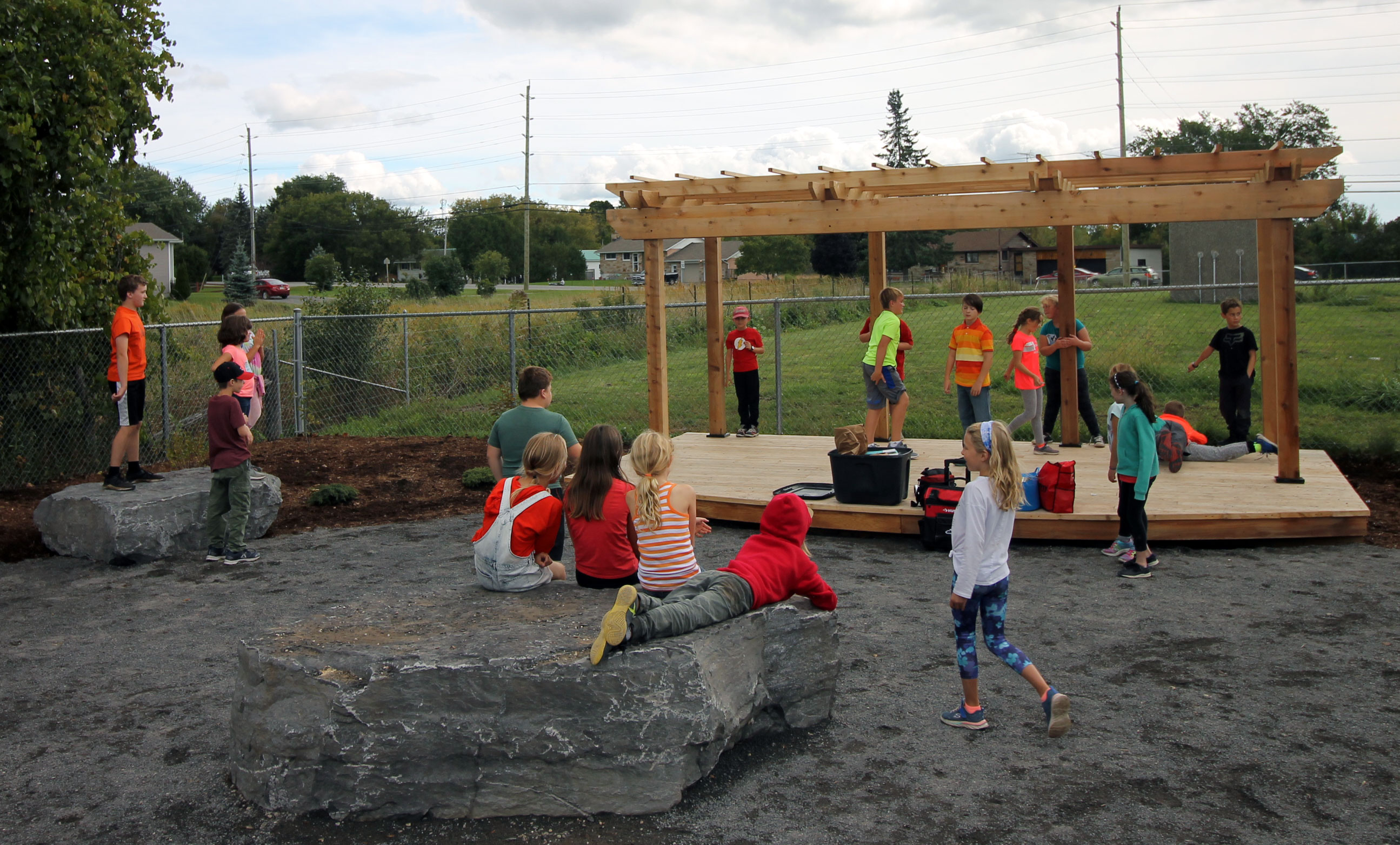Children playing with the newly unveiled cedar stage and arbour at Elginburg Public School.