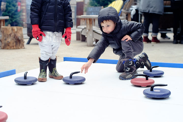 Children playing on the synthetic curling rink / Layah Glassman