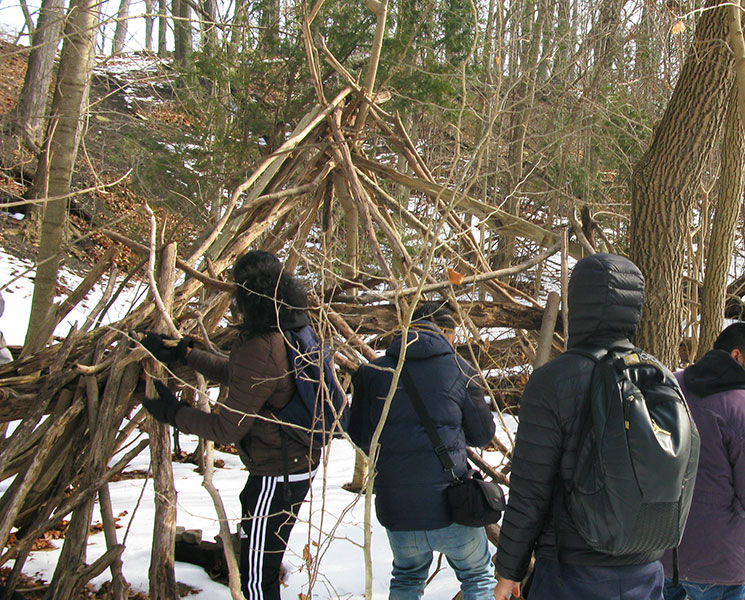 Students work together to build shelters out of found materials in the urban wilderness. Image: Arsen Kelesoglu