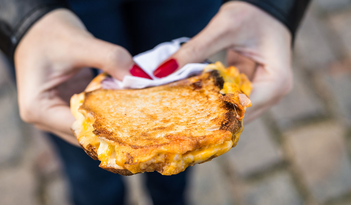Grilled cheese being held in a woman's hand.