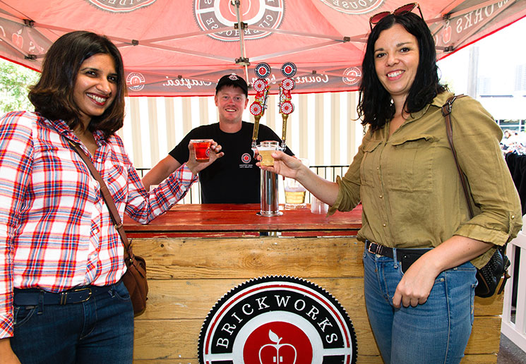 Two female friends enjoying Brickworks Ciderhouse's cider at the Harvest Apple Festival. Photo by Stanley Shoolman.
