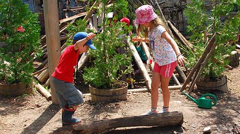 Two children balancing on a log. (Photo Credit: Mike Derblich)