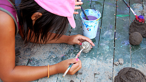 Child with paintbrush painting clay sculpture