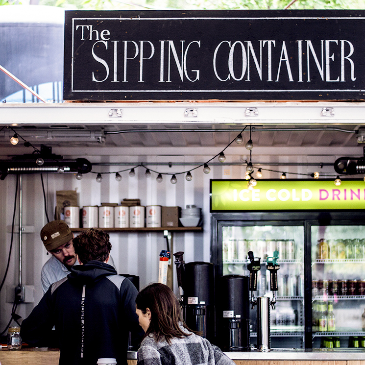 Staff pouring drinks at Evergreen Brick Works Sunday Artisan Market Sipping Container, a repurposed shipping container