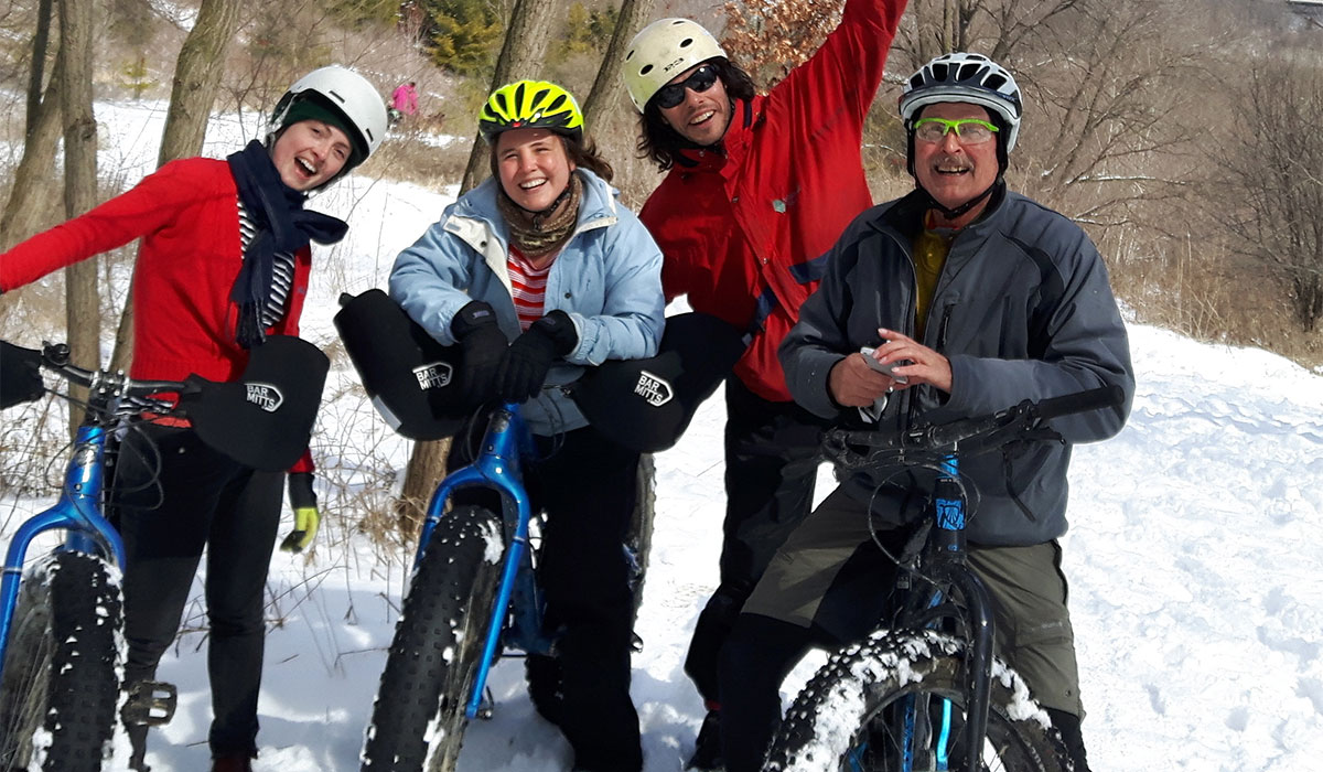 Adults smiling together with their fat bikes on a snowy winter trail.