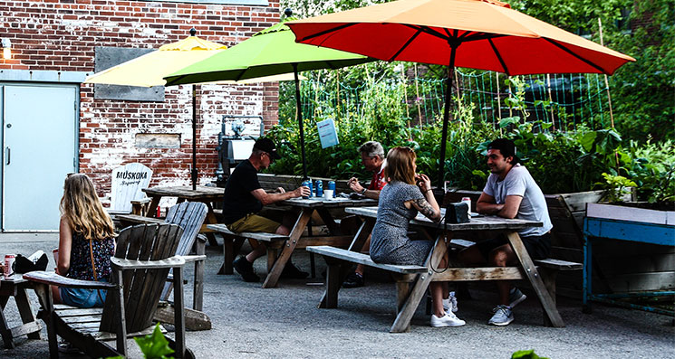 A couple sits on Mud Creek Terrace under the patio umbrellas at Summer Wednesdays.