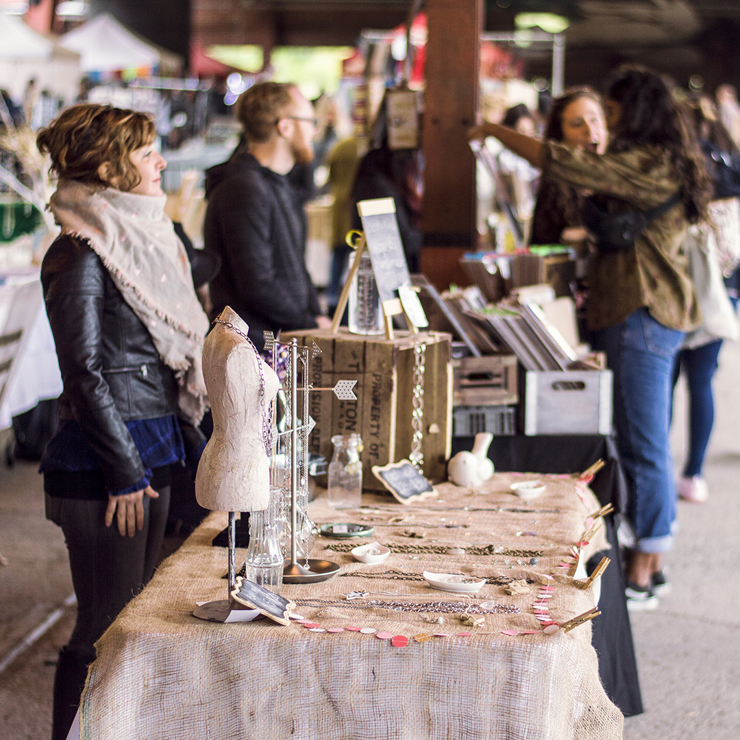 Art vendor at Evergreen Brick Works Sunday Artisan Market with silver handmade jewelry on a burlap topped table