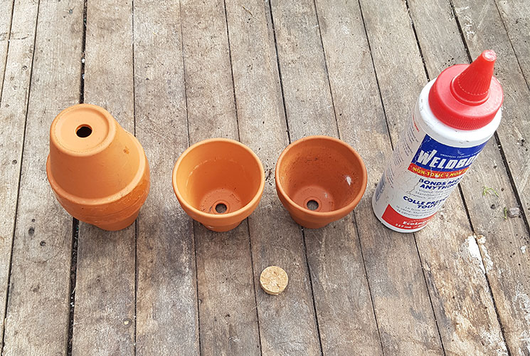 The materials you will need to build a self-watering system in your garden. Materials are two terracotta pots with holes in the bottom, a quarter inch piece of cork, and glue.