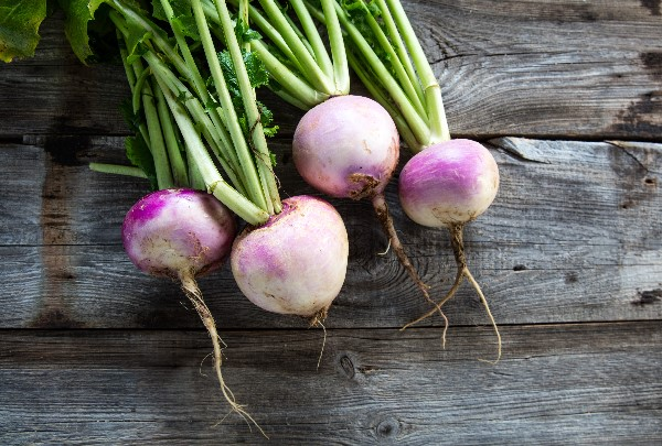 Purple topped turnips sitting on a wooden table.
