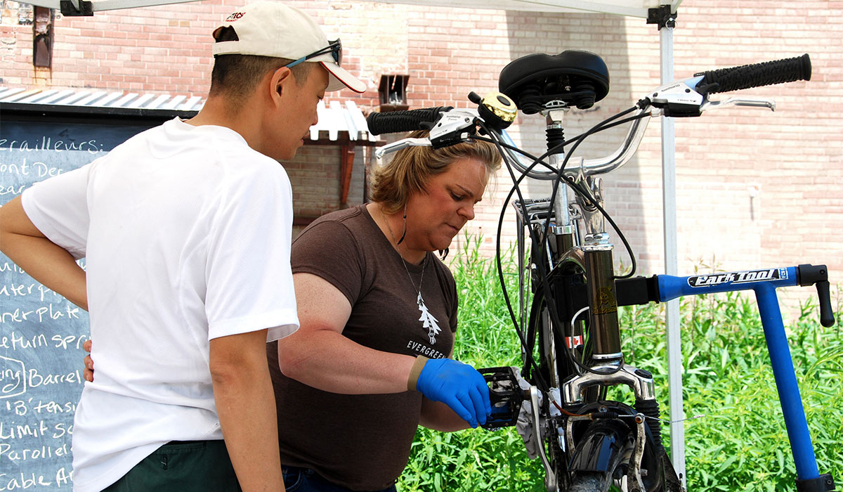 Bike Works female volunteer shows man how to fix his gears with a bicycle mounted on a rack.
