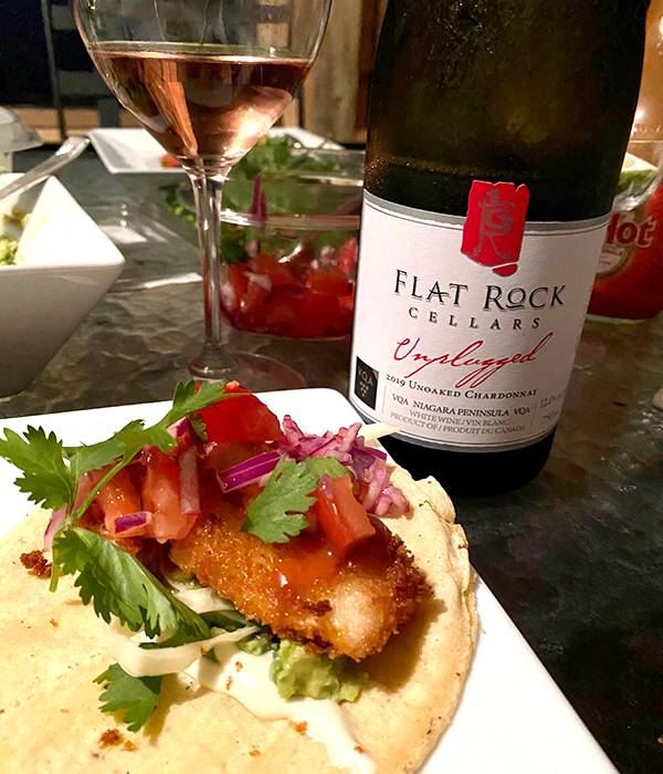 Grilled taco with battered fish, vegetables, and fresh cilantro. A bottle of Flat Rock Cellars wine.
