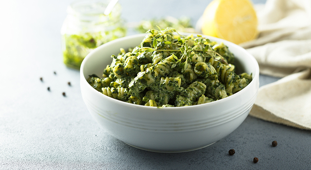 Bowl of pasta with pesto and sprouts
