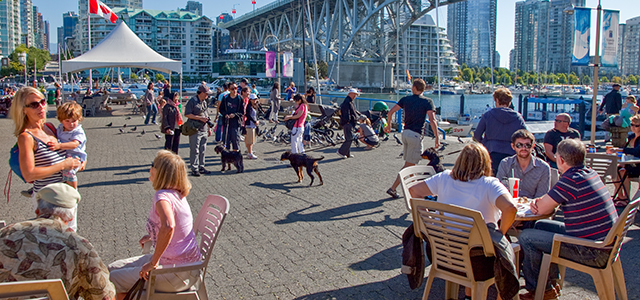Granville Island boardwalk. people sitting, walking, dogs, kids