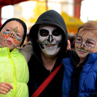An adult and two children with painted faces at the annual Day of the Dead festival at Evergreen Brick Works Image Credit: Joanne Quinn