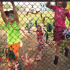 Kids climbing on a fence in their schoolyard.