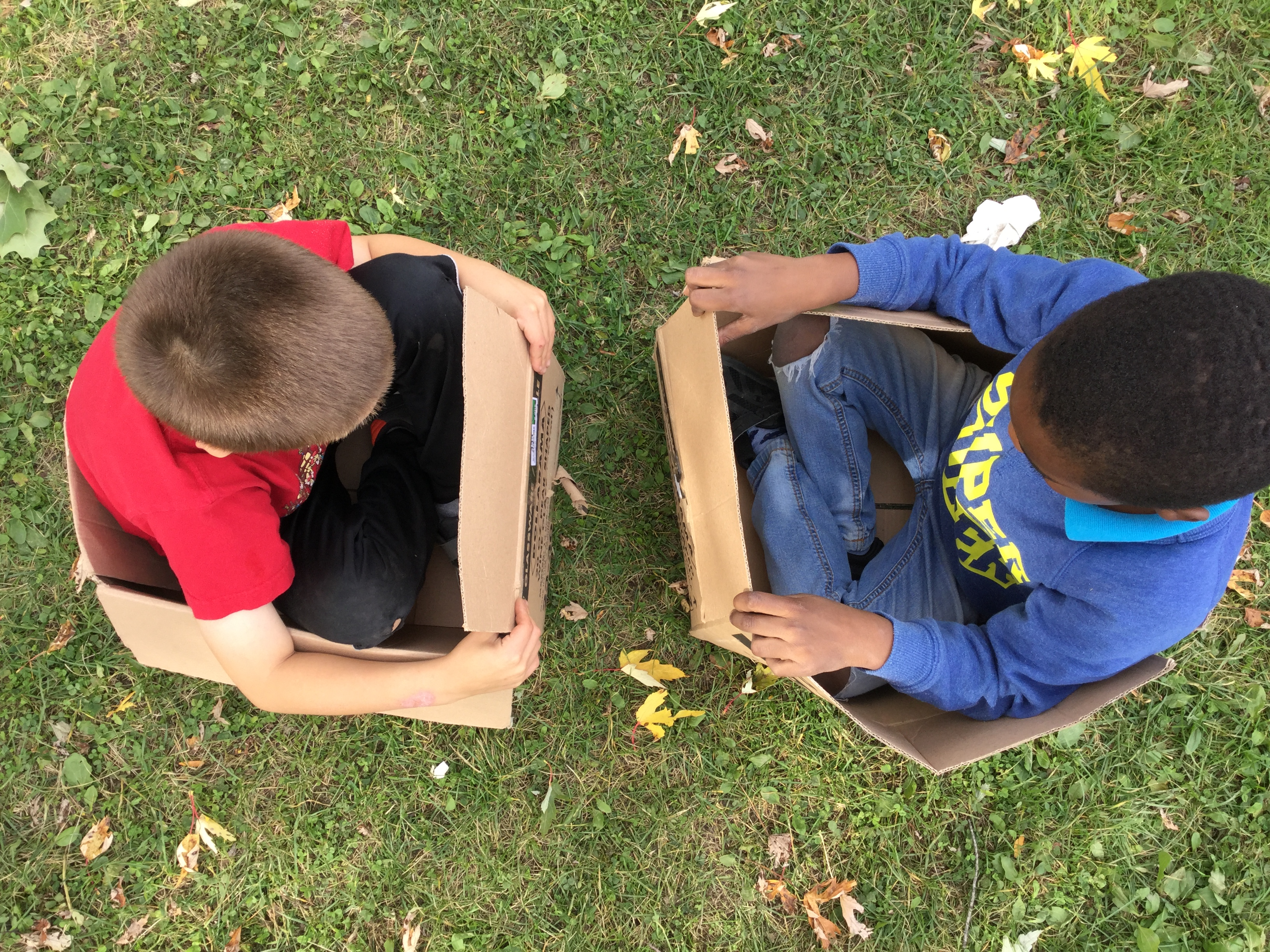 Two boys play outside sitting in cardboard boxes. Image: Joanne Burbidge