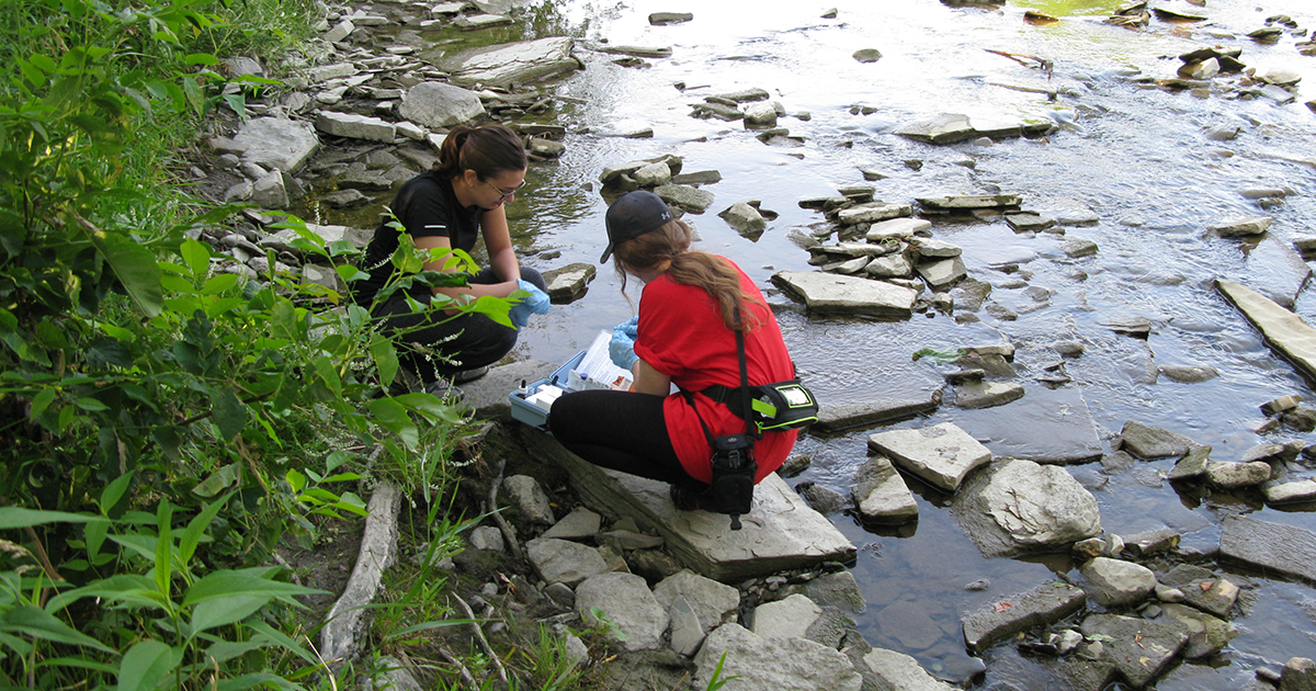 Two female volunteers inspecting and testing the river water.