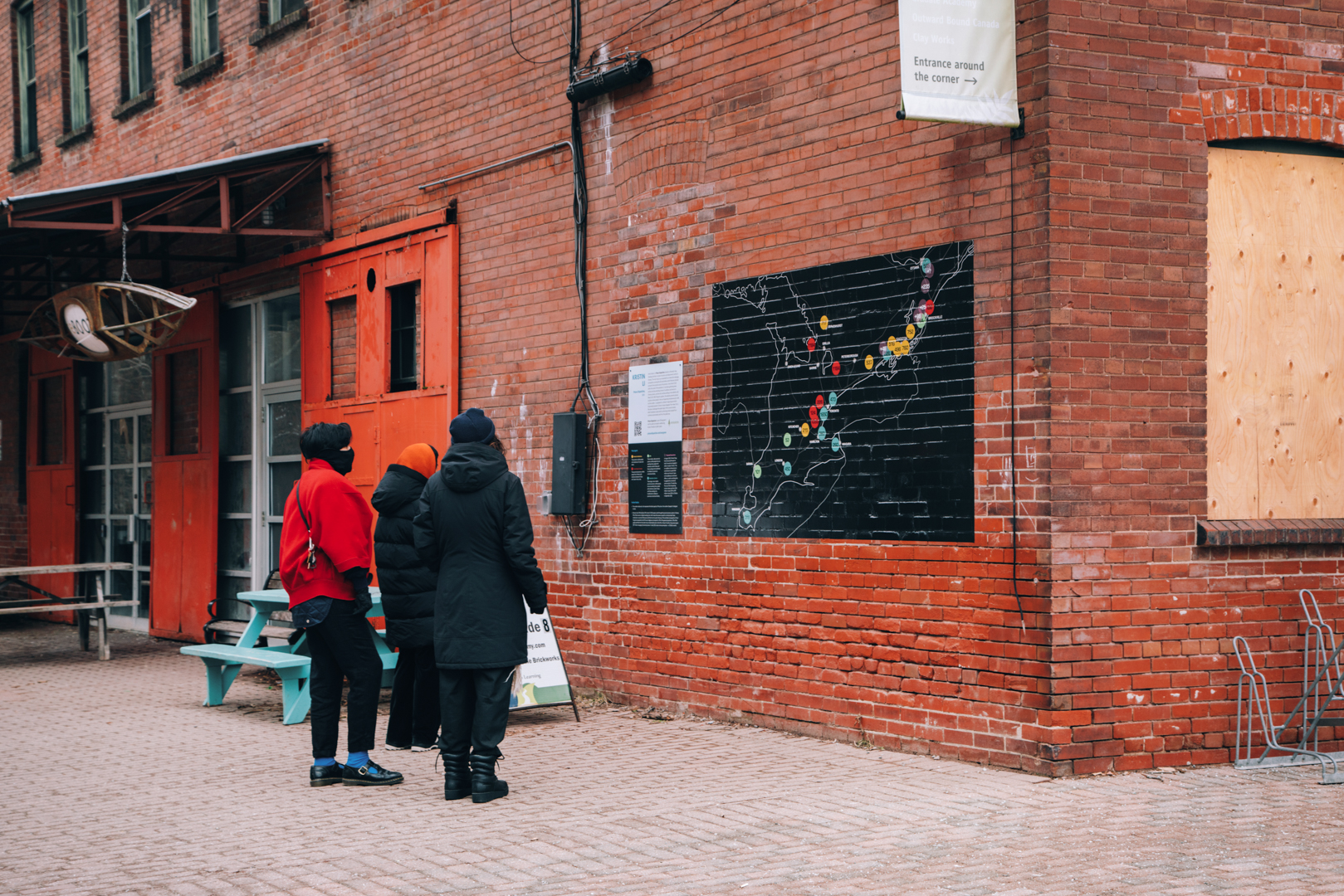Three people look at a map on the side of a brick building