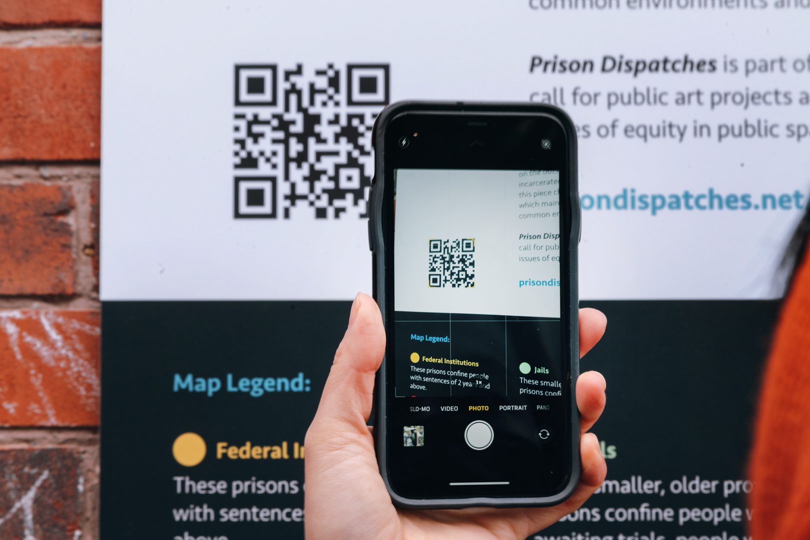 A cellphone is held in front of a qr code on a map