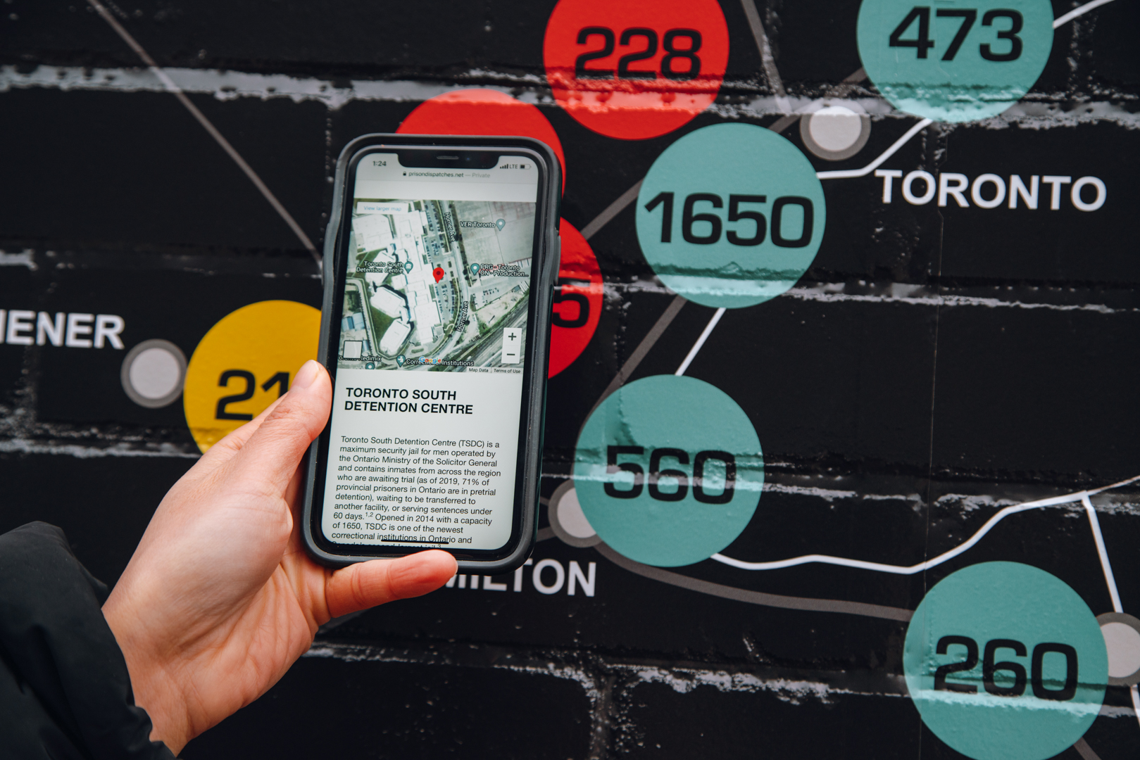 A cellphone with text explaining the Toronto South Detention Centre is help up to a map dispalying where the centre is located