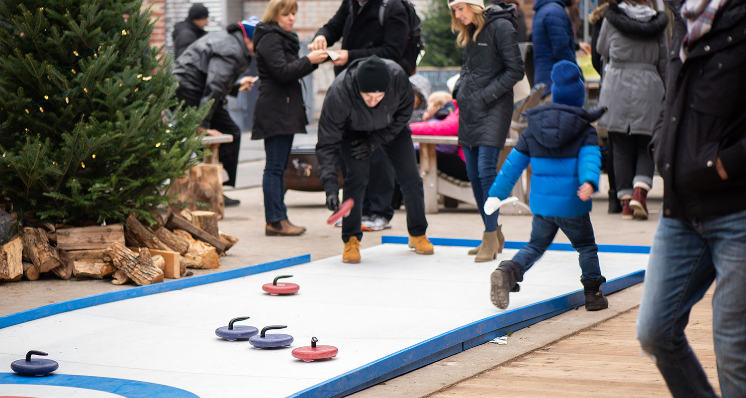 A family playing with the artificial curling rink at Evergreen Brick Works. Image: Al Yoshiki