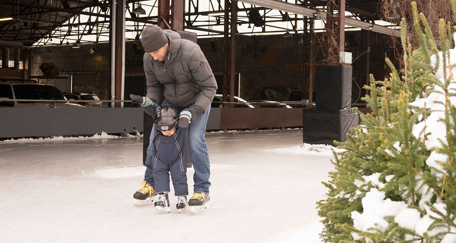 Parent holding his toddler on skating rink.