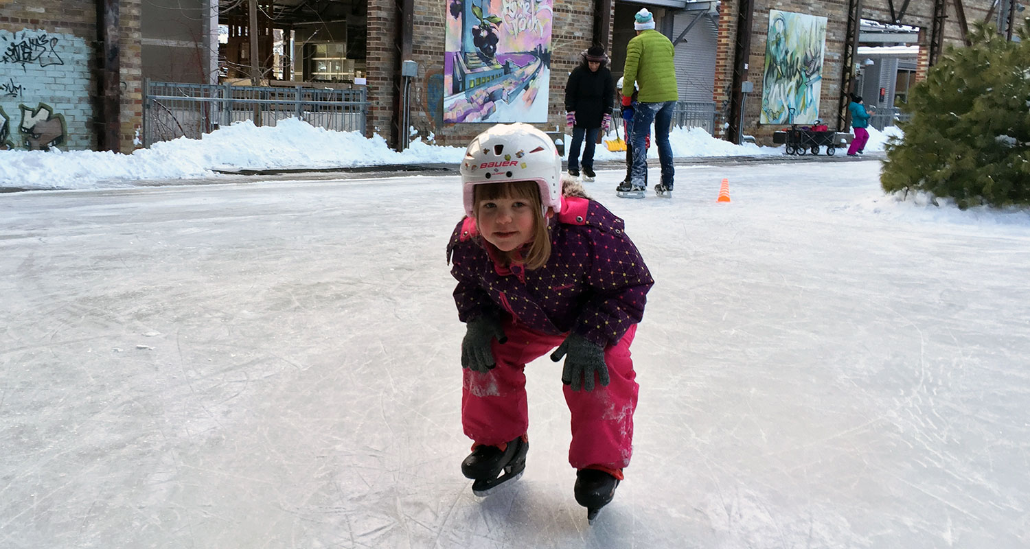 Child learning to skate on Evergreen Brick Works' skating rink.