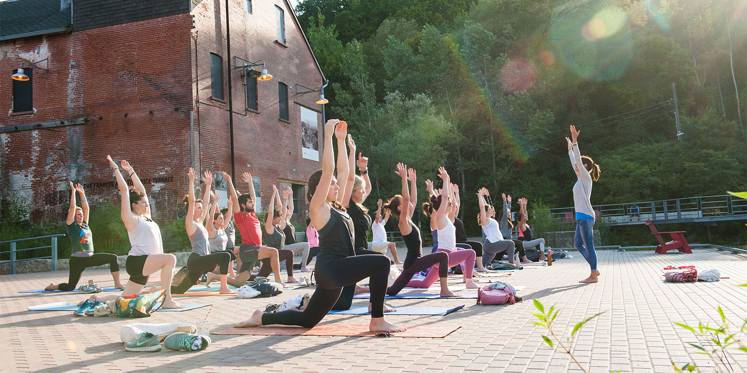 People doing yoga on the terrace at Evergreen Brick Works.