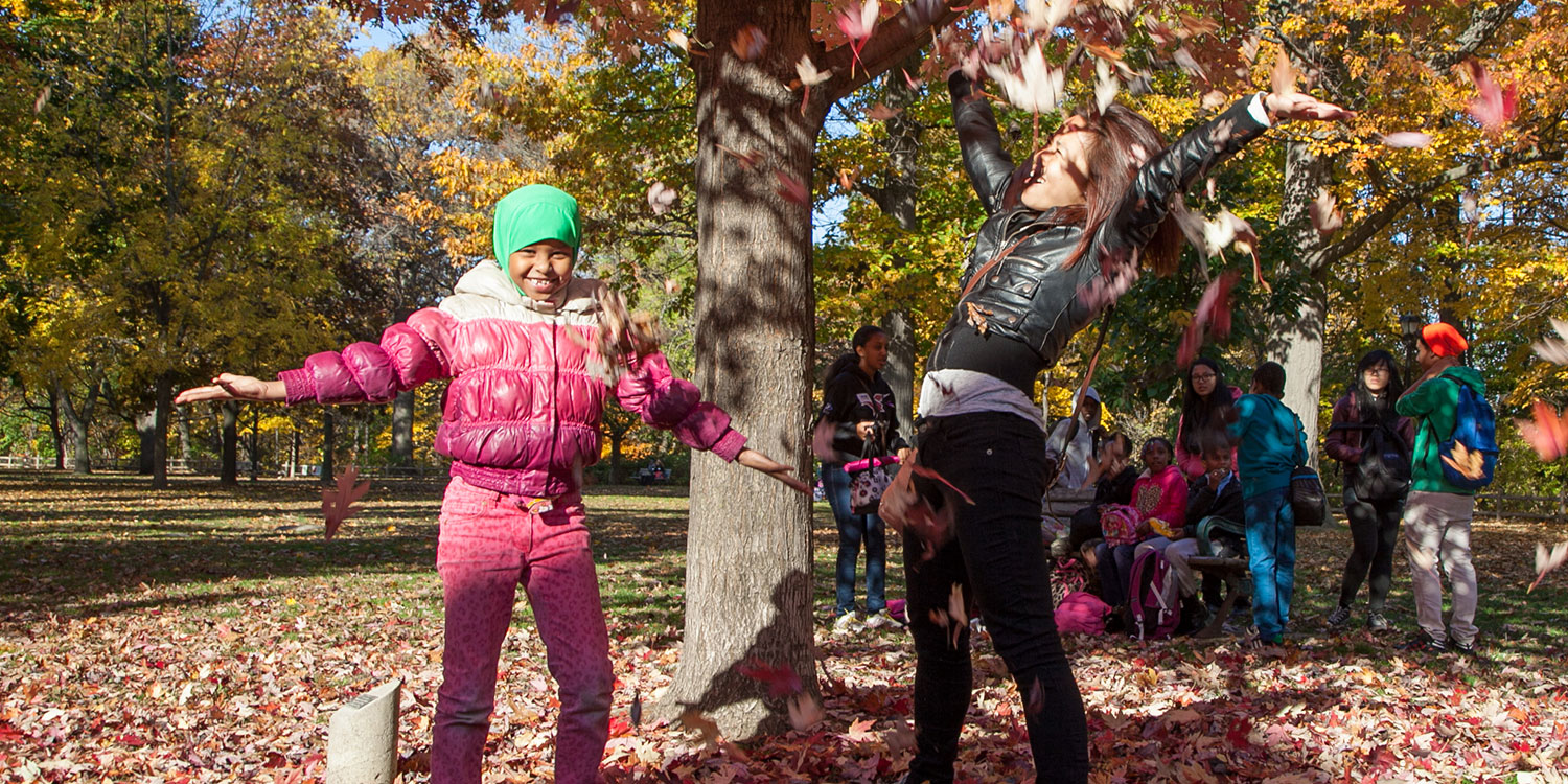 A student and teacher throwing fall leaves in the air while laughing.