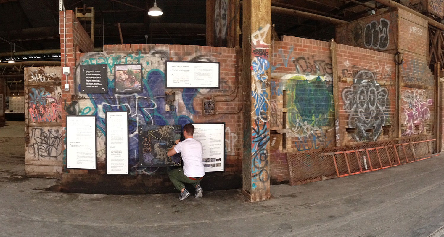 Man kneeling as he installs an exhibit in the historic kiln building at Evergreen Brick Works.