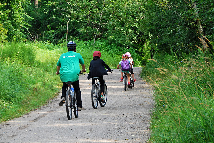 Children and volunteers biking along a trail / Mike Derblich