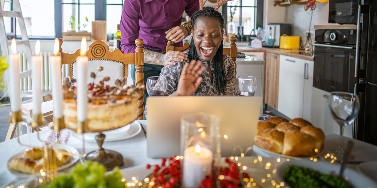 Person waving at computer surrounded by holiday dinner foods