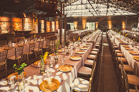 A large number of tables set for an elegant meal in the Kilns Building at Evergreen Brick Works.