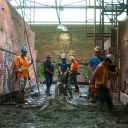 Construction workers laying new flooring between the historic kilns during the kiln building redevelopment project. Image: Bryan McBurney