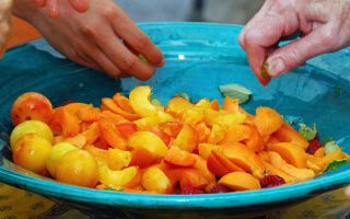 Hands sorting through mixed fruit in a bowl.