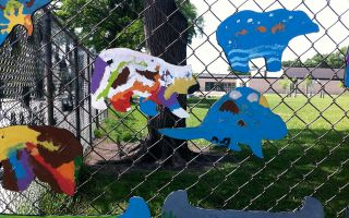 The chain link fence of a schoolyard decorated with painted wooden animals.