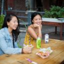 Two women sit on a picnic bench, drinking beer and eating food. Image: Al Yoshiki