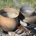 two clay pots over embers and woodfire in a grassy patch Image: Wendat vessels and image © Richard Zane Smith, 2020
