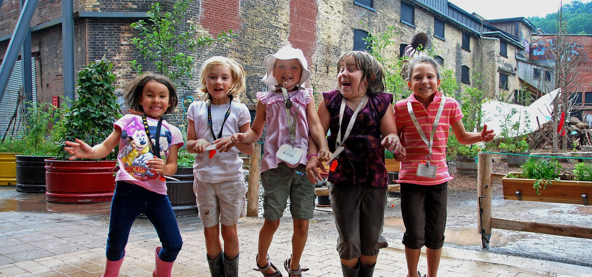 A group of girls jumping for joy in front of the Children's Garden at Evergreen Brick Works.