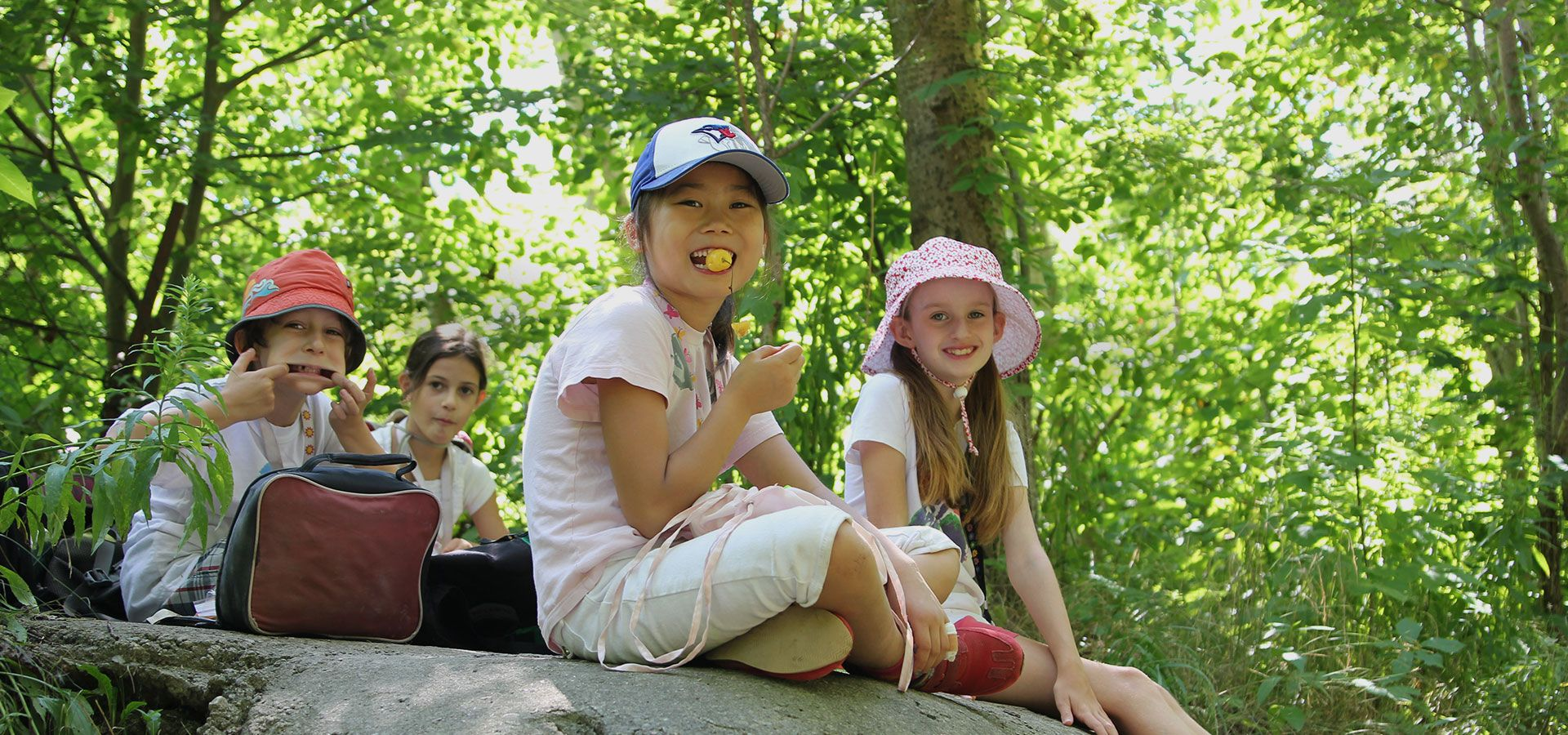 A group of children sitting on a rock in the forest at Evergreen Adventure Camp.