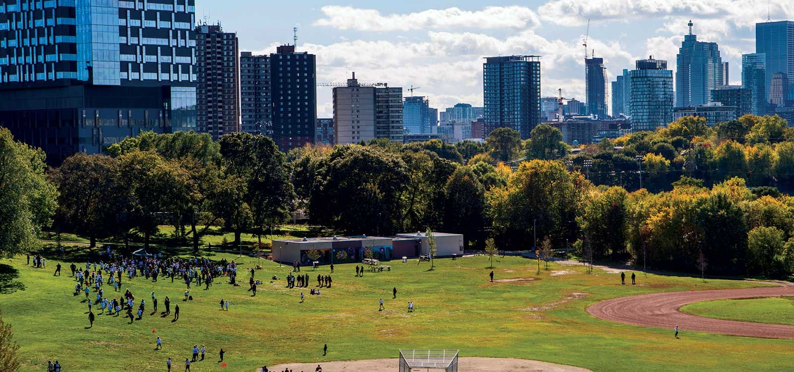 A large gathering of people in Riverdale Park, with the Toronto skyline in the background. Image: Geoff Fitzgerald