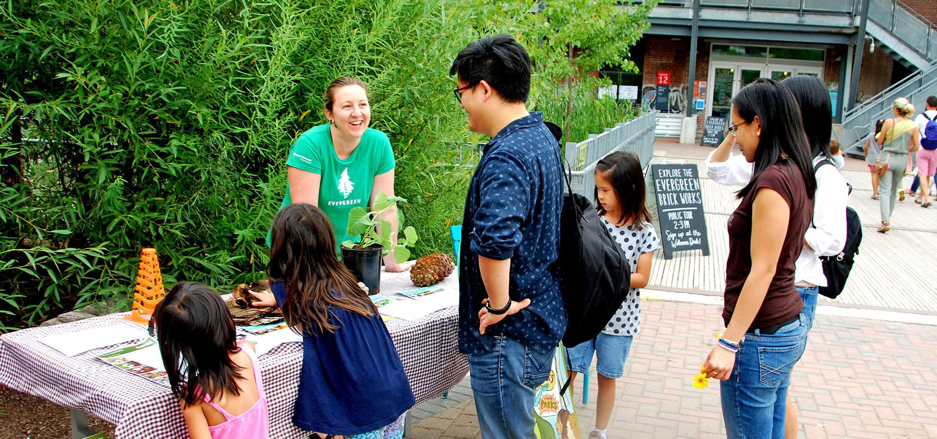 A volunteer speaking to some visitors at a display table.