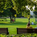 two people sitting on a park bench under the trees with family playing in the distance
