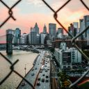 broken chain link fence in focus with the background of a city at sunset
