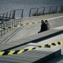 two people sitting on a bench next to a lake surrounded by caution tape
