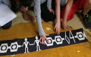 Grade 7 students at Hawthorne Village Public School gather around a Wampum belt